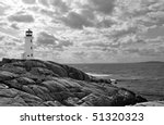 Lighthouse at Peggy's Cove, Nova Scotia.  In black and white with dramatic clouds in sky. - stock photo