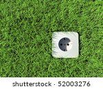 """shucko"" type F power socket in a field of grass, shot from above - stock photo"