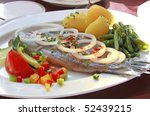 Fish dish of herring with onions, green beans, potatoes and salad garnish - stock photo