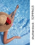 Woman in a pool hat relaxing in a blue pool - stock photo