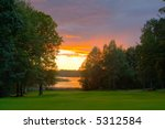 Sunset over a lakeside golf course. Excellent tone nuances achieved through HDR processing of three different exposes. - stock photo