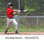 A youth baseball player takes a nice swing at the ball at home plate. - stock photo