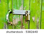 A decaying, peeling, grungy green garage door with a lock - stock photo