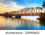 Iron Toll Bridge Over River At Sunrise - stock photo