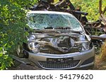 A sight of a car broken in a car crash with scorched ruins on the background - stock photo