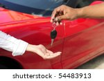 car dealership: woman receiving car key from salesman - stock photo