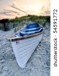 White hull lifeguard rowboat on white sand beach at sunset - stock photo