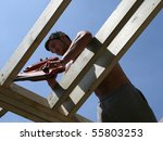 A construction worker uses a nail gun - stock photo