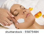 Young beautiful woman receiving a facial - stock photo