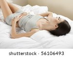 Young woman stroking her belly; bellyache or constipation - stock photo
