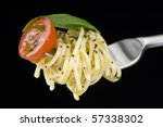Spaghetti with tomato and basil on fork, black background - stock photo