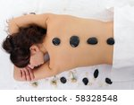 Woman getting spa treatment isolated on white. Massage with hot stone - stock photo