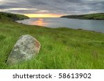 A rock in a grassy field near the ocean. - stock photo