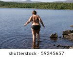 Overweight woman going into a tarn to take a swim - stock photo
