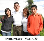 Family from four stands on grass against house - stock photo