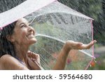 Beautiful young woman grins as she holds out her palm to catch falling water. She is holding an umbrella over her head. Horizontal shot. - stock photo