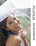 Beautiful young woman smiles towards the camera while holding an umbrella under a spray of water. Vertical shot. - stock photo