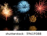 Bursts of colorful fireworks reflecting in water - stock photo