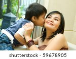 asian ethnic boy kiss his happy mother - stock photo