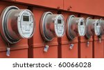 Line up of five electric power meters on red electrical panels - stock photo