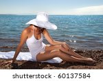 Tanned girl in a white dress and white hat on the beach - stock photo