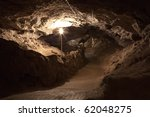 A dark cave with a pathway in the city of Kungur, Russia - stock photo