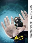 Adult male scuba diver showing the palms of his hands underwater. Focus on the divers' face. Ras Ghozlani, Sharm el Sheikh, Red Sea, Egypt. - stock photo