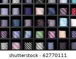 Wonderful background shot of a multi-coloured collection of rolled-up ties, in a retail setting. - stock photo