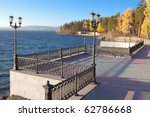 Shore of the lake with a molded fence - stock photo