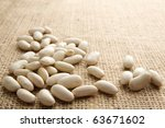 White beans scattered on burlap with copy space - stock photo