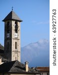 Old Italian bell tower in village with mountains in the distance - stock photo