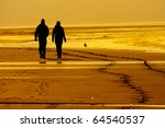 silhouettes of a couple at beach in sunlight - stock photo