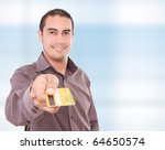 Young man giving his credit card looking at the camera,  blue background - stock photo