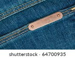 Bronze metal label on blue jeans - stock photo