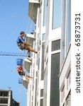 washing window cleaning men Industrial mountaineering building city - stock photo