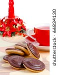 Cup of red tea, chocolate iced cookies and christmas decorative candle isolated on white - stock photo