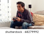 Young Man Playing Video Games on Sofa - stock photo