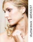 Beautiful Blond bride wearing diamond jewelery looking away - stock photo
