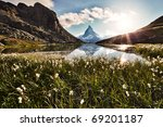 Matterhorn reflected in the Riffelsee and shiny backlit flowers - stock photo