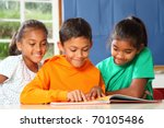 Primary school children in class reading learning - stock photo