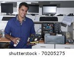 Small business: computer technician with motherboard at workshop - stock photo