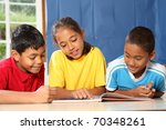 Primary school kids learning together in classroom - stock photo