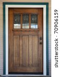 Craftsman deco style window in mission style stained wood door with green and white trip - stock photo
