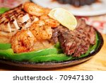 Fajitas in metal pan on wooden plank, shallow focus - stock photo