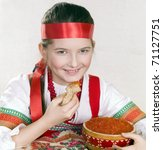 girl in Russian national clothes with a bowl of red caviar and a pancake in a hand. - stock photo