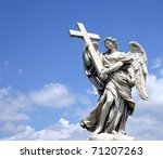 Holy statue of carved winged angel with cross in blue sky and clouds - stock photo