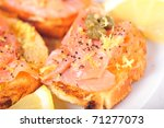 Salmon brushetta with capers and lemon - stock photo