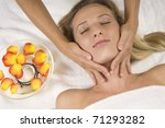 Young beautiful woman receiving a facial massage - stock photo