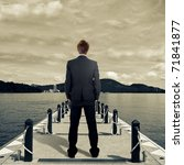Business man standing on dock near lake. - stock photo