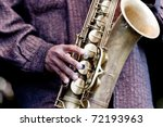 Hand of musician playing jazz saxophone during live performance on stage - stock photo